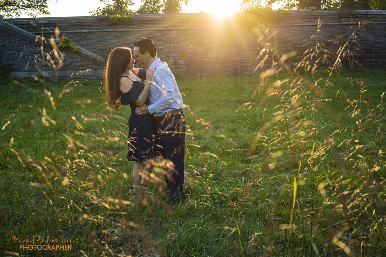 couple kissing playfully at sunset during engagement session